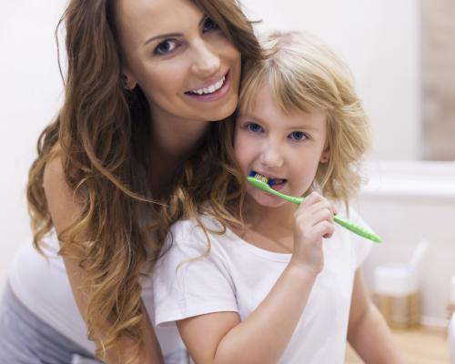 Mother helping daughter brush teeth